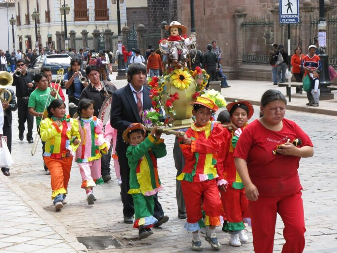 Children in colourful costume carry a tiny child Jesus on a platform