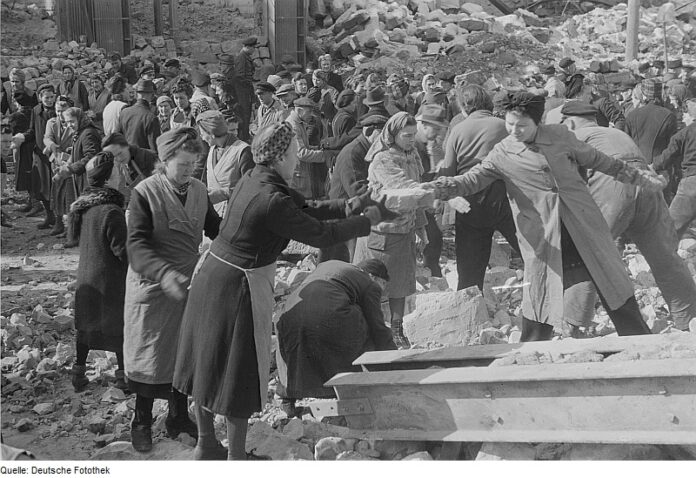 women cleaning bricks from demolished buildings and passing them hand to hand for construction in new buildings
