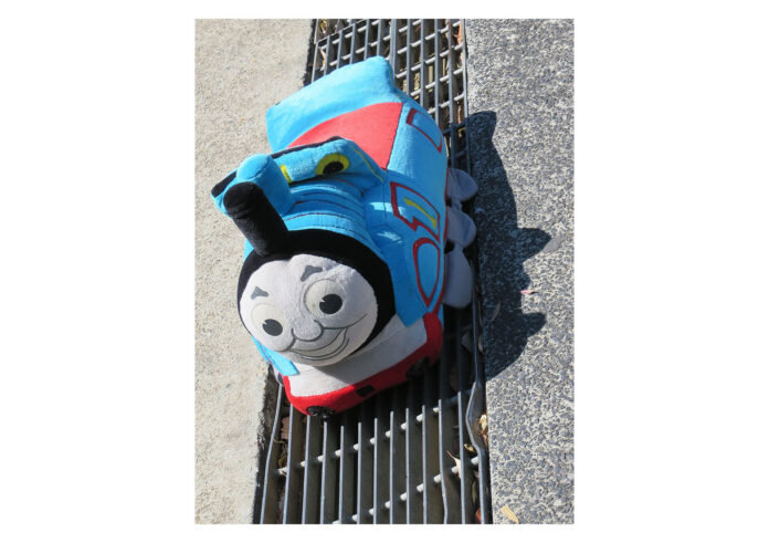 A colourful child's toy engine sits on the tracks of a pavement drain