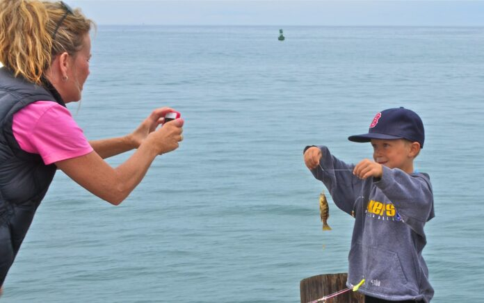 By the waterside, a mother proudly photographs a tiny toddler of a fish held aloft by a five-year-old-ish fisherman