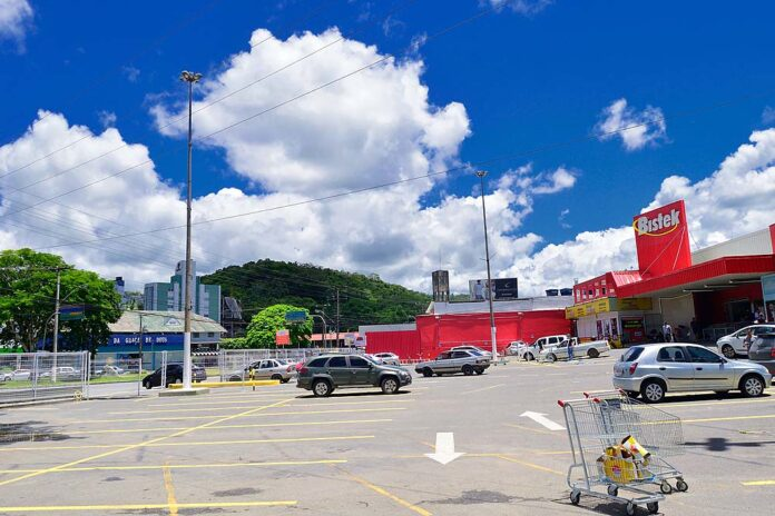 A big, practically empty parking lot stretches in front of a suburban supermarket