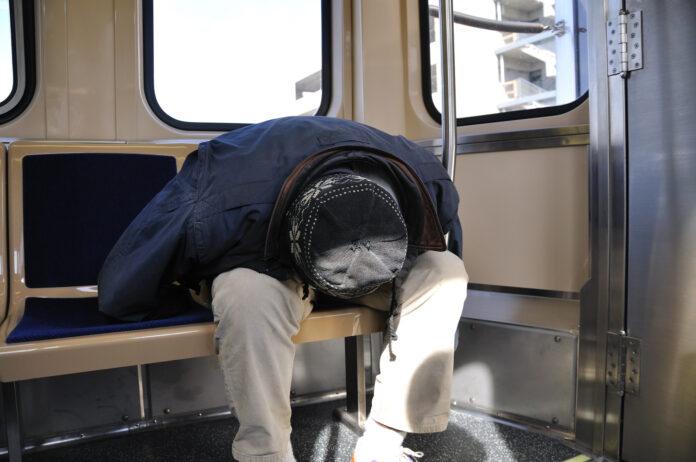 A n sits on transit seat, head between knees, in sleep