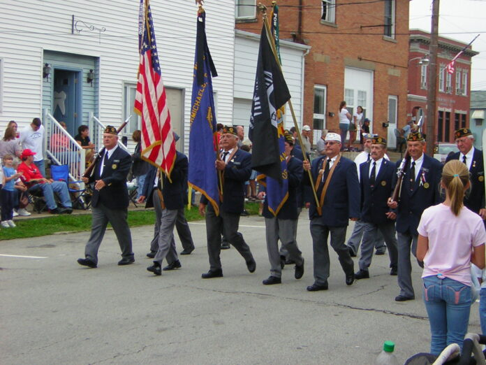 A veterans parade, with its participants, carrying US and unit flags, as well as rifles. They are clad in blue blazers and grey flannels.