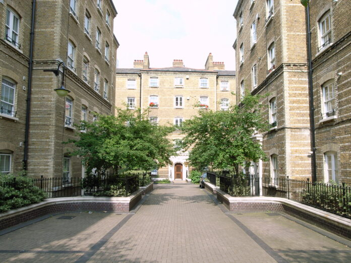 A quiet courtyard between four story high, elegant off-white buildings