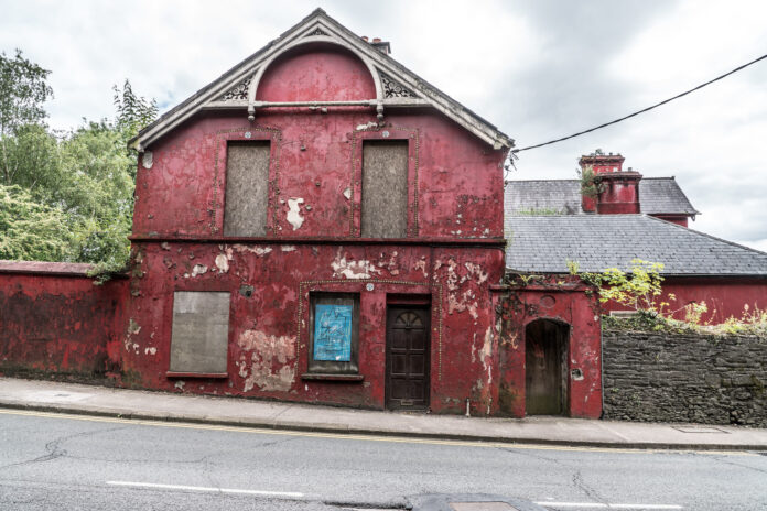 A plaster sided home paint in faded and chipped red beside a road