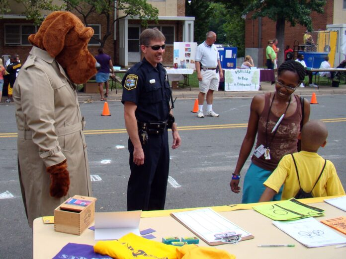 A police officer, a raincoat person wearing a large dog head, a mother and child all gather in front of a community day stalll