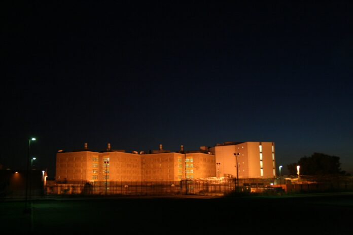 A forbidding prison building painted orange by bright floodlights