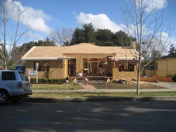 Across a residential street a half-finished bungalow is all chipboard panels and exposed timber studs