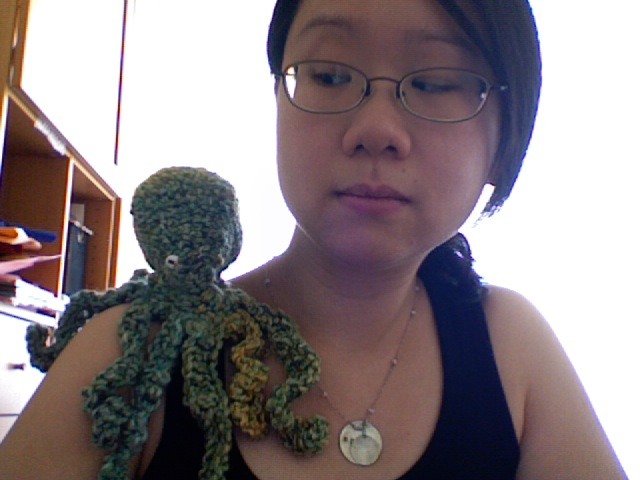 A young woman looks doubtfully at knitted octopus perched on her shoulder