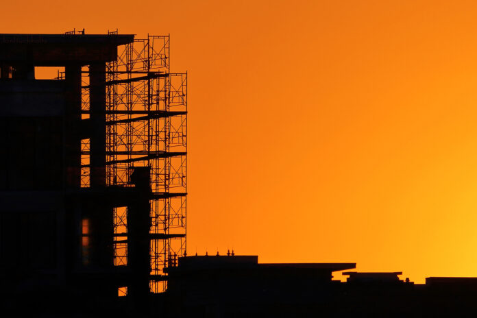 a new building under construction is a latticework of black set against an orange sunset