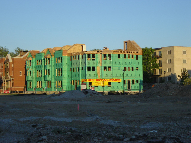 A series of conjoined row houses under construction is a cheery picture of green, as the bright coloured insulation waits to be covered up with more substantial red brick.