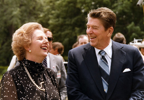 Margaret Thatcher and Ronald Reagan laugh together at an outdoor gathering
