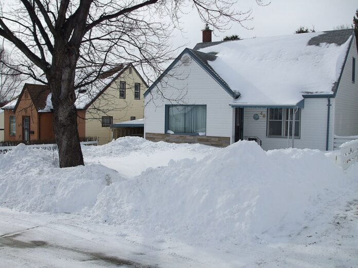 house nestled in metre high snow banks