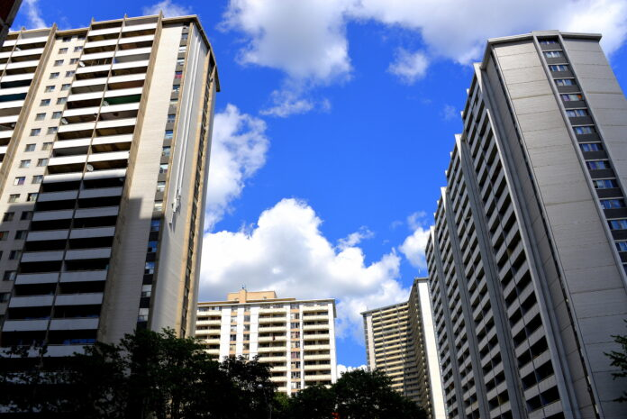 Tall cream-coloured high rise apartment tower above the camera